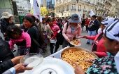 People receive a free meal at soup kitchens set up on a street during a demonstration against the government's economic measures in Buenos Aires, Sept. 11, 2018.
