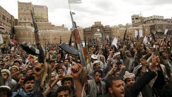Rebels hold up their weapons during a rally against air strikes in Sanaa, Yemen, March 26, 2015.