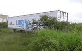 An officer walks past an abandoned trailer full of bodies in Tlajomulco, Jalisco, Mexico Sept. 15, 2018 in this still image taken from a video obtained September 17, 2018