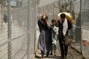 A family coming from Afghanistan walk down a corridor between security fences at the border post in Torkham, Pakistan June 18, 2016.