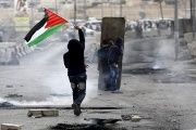 A Palestinian protester holds a Palestinian flag as others take cover during clashes with the Israeli army at Qalandia checkpoint near occupied West Bank city of Ramallah, Oct. 6, 2015.