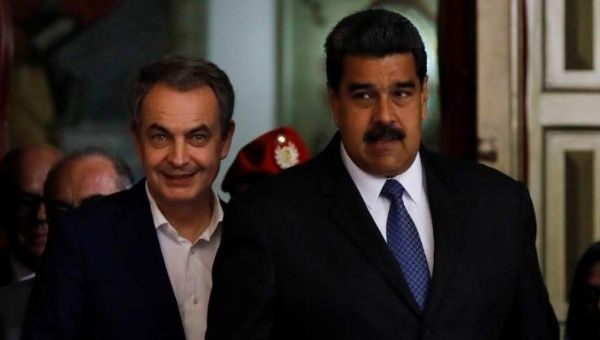 Zapatero (L) offers to mediate talks between Maduro (R) and opposition.