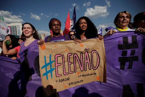 "Women hold a sign that reads ""Not Him. Love. Tolerance. Respect,"" during the demonstration in Brasilia."