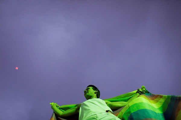 A man holds the flag representing the LGBT community at the protest in Rio de Janeiro..