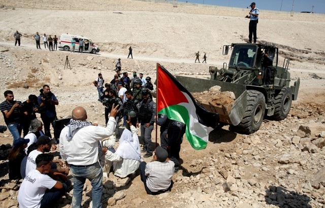 Palestinians protest in front of an Israeli bulldozer against Israel's plan to demolish the Palestinian Bedouin village of Khan al-Ahmar, Sept. 14, 2018.