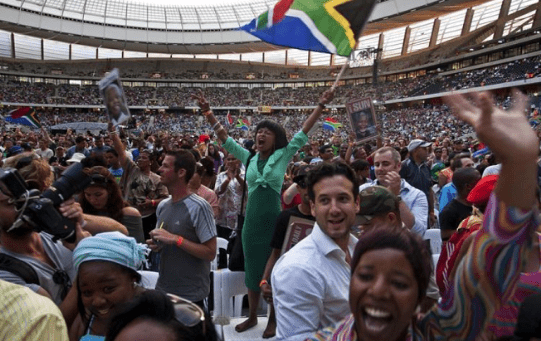 "A woman flies a South African flag during the ""Nelson Mandela: A Life Celebrated"" memorial service at Cape Town Stadium Dec. 11, 2013"
