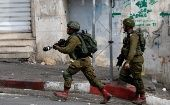 Israeli soldier runs during clashes with Palestinians in Hebron, in the occupied West Bank