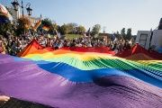 Participants display a large rainbow flag at the