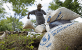 A farmer moves bags of provisions, donated by the U.N. World Food Programme (WFP), during food aid distribution to families affected by a drought, Aug. 28, 2014.