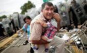 A Honduran man protects his child after fellow migrants stormed a border checkpoint in Guatemala.