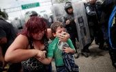 A Honduran migrant, part of a caravan trying to reach the U.S., protects her child