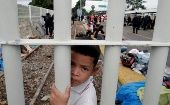 A Honduran migrant child, part of a caravan trying to reach the US, looks though the gate on the bridge that connects Mexico and Guatemala in Tecun Uman, Guatemala, October 20, 2018.