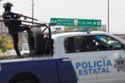 A police agent keeps watch atop a truck at a checkpoint on the outskirts of Reynosa.