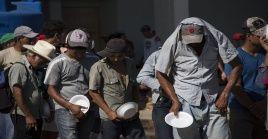 Integrantes de la caravana de migrantes centroamericanos que se dirigen a Estados Unidos hacen fila para recibir alimentos el municipio mexicano de Juchitán.