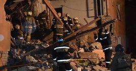 Unidades de bomberos realizan operaciones de búsqueda y rescate en los escombros del edificio.