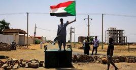 Un manifestante sudanés sostiene una bandera nacional en una calle bloqueada de Jartum.