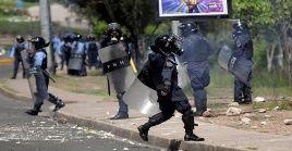 Policías reprimen las movilizaciones en Honduras contra el presidente Juan Orlando Hernández.