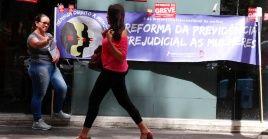 Mujeres brasileñas entregan volantes en contra de la reforma jubilatoria.