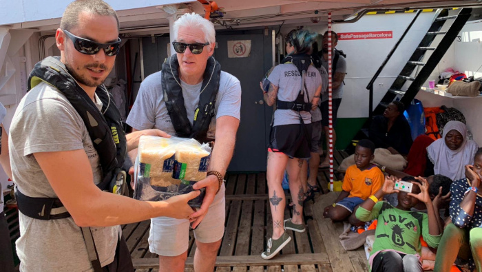 El actor Richard Gere ayuda a transportar suministros a bordo del barco de rescate Open Arms.