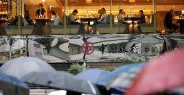 Comensales en un restaurante ven pasar una marcha contra la ley de extradición en Hong Kong.