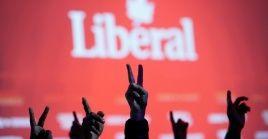 Militantes del Partido Liberal de Canadá hacen la señal de la victoria mientras miran los resultados de los comicios.