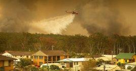 Un helicóptero del Servicio Rural de Bomberos descarga agua sobre los incendios que arrasan los bosques de la ciudad de Harrington (Australia).