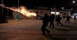Funcionarios del Esmad lanzan bombas contra manifestantes en Bogotá.