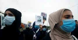 Universitarios llevan fotos de personas que fueron asesinadas en una protesta contra el Gobierno de Irak.