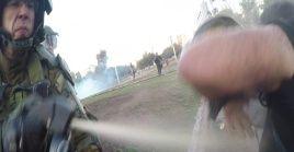 El mayor J. Muñoz. G., de Carabineros, rocía gas lacrimógeno al camarógrafo de teleSUR, Ítalo Retamal.
