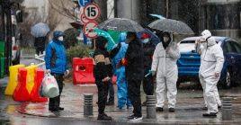 Personal médico espera la llegada de pacientes por coronavirus afuera de un hospital en la ciudad china de Wuhan.