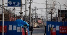 Voluntarios de seguridad pública usan cubrebocas mientras hacen guardia en la entrada de una comunidad rural de China.