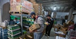 Voluntarios palestinos llenan cajas con suministros de comida donados a familias cristianas, en un almacén en la ciudad cisjordana de Belén.