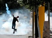 Un manifestante devuelve una granada de gas a las tropas israelíes durante protestas, el viernes, en Hebrón, Palestina.