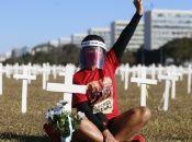 Una activista porta una mascarilla y careta mientras permanece sentada entre cruces colocadas simbolizando a las personas que han fallecido por la Covid-19 en Brasil.
