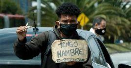 Un hombre vende dulces y pide ayuda en un semáforo en Bogotá, capital de Colombia.
