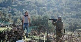 Un jóvenes palestino es amenzado por un soldado israelí durante una protesta semanal en Cisjordania.