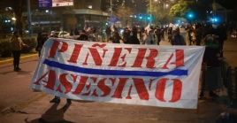 En Santiago unas 50 personas concentradas en Plaza Ñuñoa portaban pancartas que exigían la renuncia del presidente.