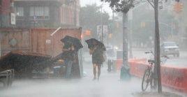 Dos personas caminan bajo el fuerte viento y la lluvia durante la tormenta tropical Isaías en Nueva York.