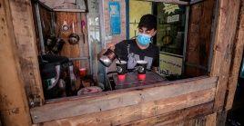 Un palestino con una mascarilla vende café y té en medio de la pandemia de Covid-19 en la ciudad de Gaza.