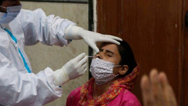 Un paramédico toma una muestra de un comerciante de Cachemira para realizar su prueba rápida de antígeno para la Covid-19.