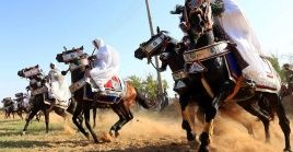 """Los jinetes usan el """"jardín"""", una gran sábana blanca que portan atada al cuerpo como toga romana en el Festival de Caballo de Trípoli."""