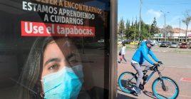 Un hombre circula en bicicleta junto a un anuncio que fomenta el uso del cubrebocas, en Bogotá, Colombia.