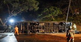 En las imágenes difundidas por la prensa local se ve el autobús volcado de costado, en medio de los restos de la valla de seguridad.