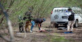 Funcionarios del Servicio Médico Forense (Semefo) analizan los cuerpos de los presuntos sicarios asesinados.