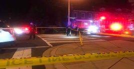 Funcionarios policiales acordonan el área donde ocurrió el tiroteo que dejo tres muertos y tres heridos.
