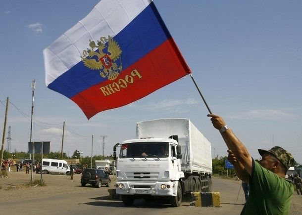 A local resident holds a Russian national flag as lorries, part of a Russian humanitarian convoy crosses into Ukraine. (Photo: Reuters)