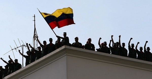 Venezuelan soldiers loyal to Hugo Chavez wave the country's flag atop their barracks after retaking the presidential palace from the de facto regime, April 13, 2002.