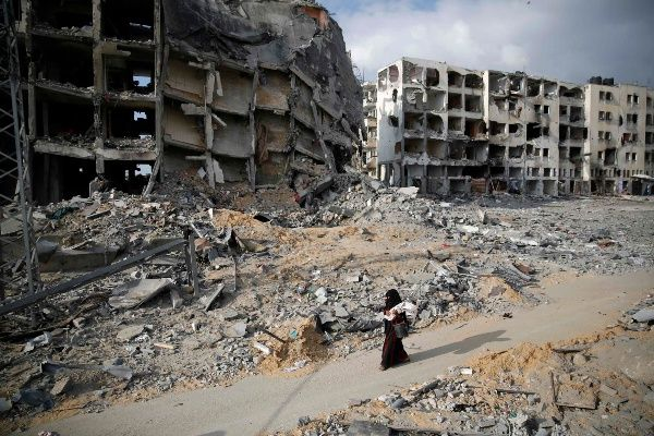 A Palestinian woman walks past buildings destroyed by what police said were Israeli air strikes and shelling in the town of Beit Lahiya in the northern Gaza Strip August 3, 2014. (Photo: Reuters)