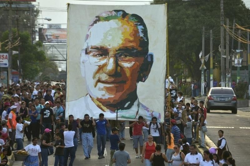People march through San Salvador holding a banner commerorating Oscar Romero