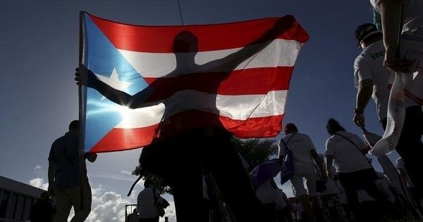 A protester holding a Puerto Rico's flag takes part in a march to improve healthcare benefits in San Juan.